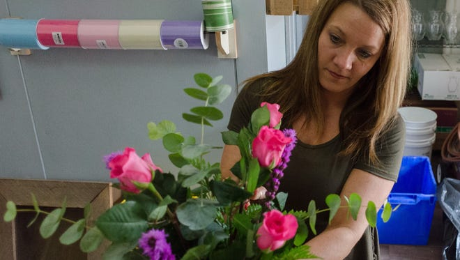 Leaning Lily owner Amber Mills puts together a flower arrangement at her shop on April 19, 2017 in Richmond, Ind.'s Historic Depot District.