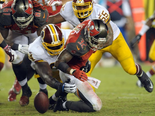 Tampa Bay Buccaneers running back Jeff Demps (32) fumbles the ball after being hit by Washington Redskins defensive tackle Clifton Geathers (94) during the fourth quarter of an NFL preseason football game Thursday, Aug. 28, 2014, in Tampa, Fla. The Buccaneers recovered the ball. (AP Photo/Steve Nesius)