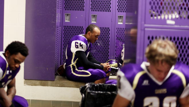 Waynesboro High School senior KK Germany, center, waits in the locker room for the coach before the kickoff at Friday's homecoming game against Broadway High School on Friday, October 10, 2014.