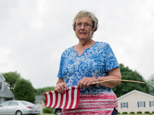 Smyrna Mayor Joanne Masten on Friday holds one of the flags installed on Carter Road that had been found to have been broken. Someone was arrested for stealing flags in the same area last year.