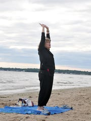 Donna Lueke, who has been a yoga instructor for the last 15 years, demonstrates a pose during one of her classes at East Harbor State Park beach Tuesday morning.