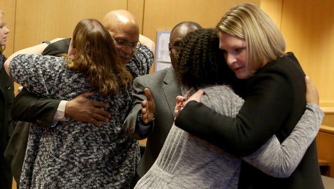 Darryl Eason, an attorney for Elaina L. Brown, hugs co-defendant Kelly Williams as her attorney, Deanna Kelley, hugs Brown after a hearing in front of Judge Kenneth King. King ruled that the felony counts -- involuntary manslaughter and second-degree child abuse charges -- against the two Michigan Department of Health and Human Services Child Protective Services workers were insufficient and dismissed those charges.
