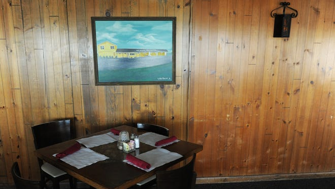 A table is set and waiting for the next dinner hours under a painting of the restaurants exterior at Wright's Family Restaurant on Thursday, Aug. 25, 2016. After 45 years in business, Wright's is closing on Oct. 2nd.