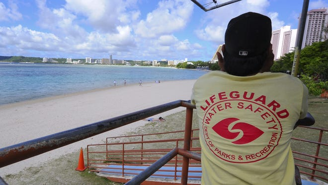 In this 2014 file photo, a lifeguard watches over beach-goers at Ypao beach.