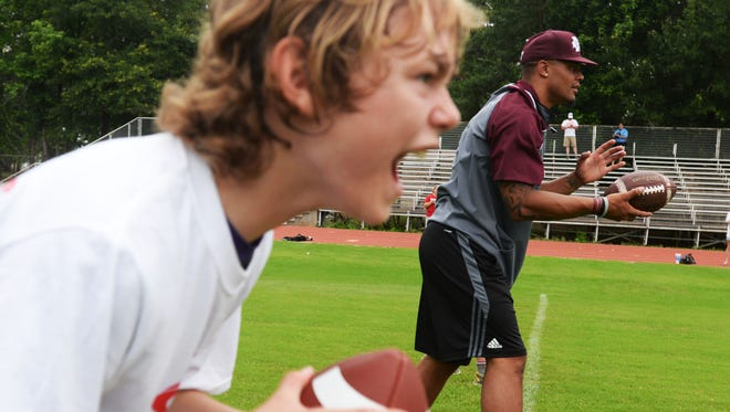 Aiden Riley (left) participated in a football camp with Dak Prescott (right) at Haughton in 2015.