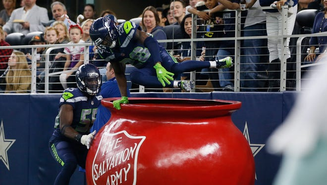 Justin Coleman, then with Seattle, leaps into the Salvation Army kettle as defensive end Frank Clark looks on in 2017. Coleman recorded a pick-6 against Dallas' Dak Prescott.