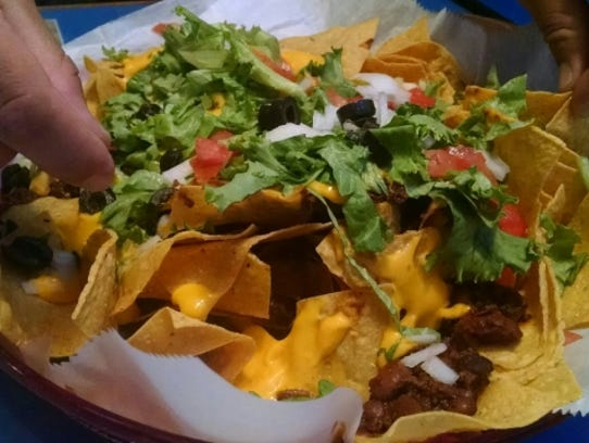 Lefty's nachos with the works includes cumin rich beef