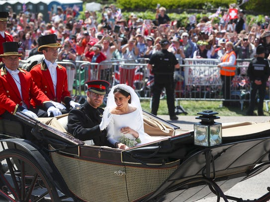 Britain's Prince Harry and his wife Meghan Markle ride