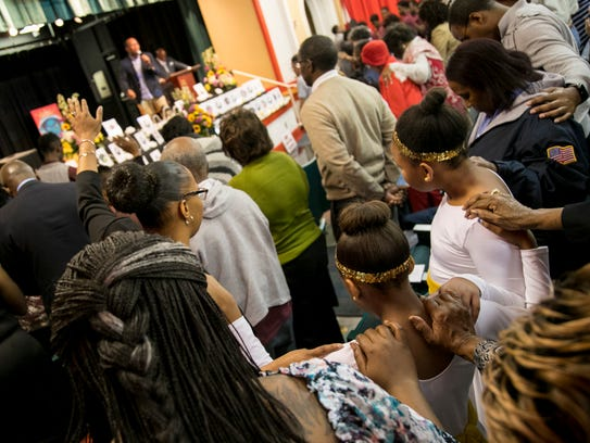 Audience members join pastor Zurial Johnson in the