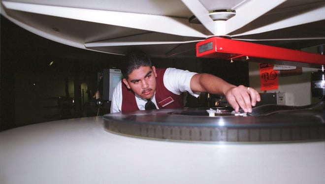 Matthew Flores, a projectionist for Carmike Cinemas, makes an adjustment to a film platter which holds the feature-length movie.