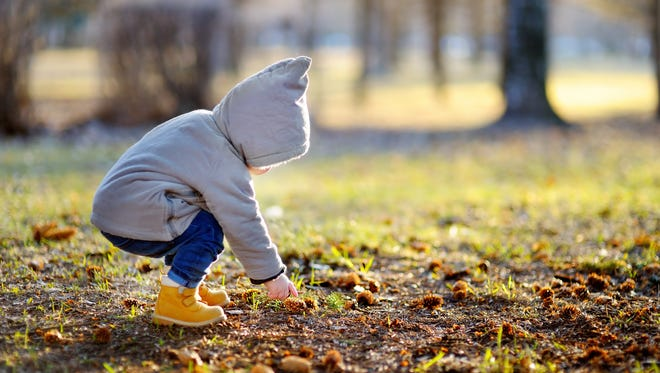 Toddler boy walking outdoors at the warm spring day, focus on child hand