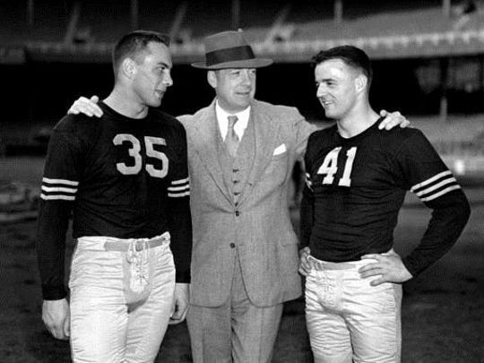 FILE - In this Oct. 25, 1946, file photo, Army football coach Earl Blaik, center, stands with his co-captains Felix Blanchard, left, and Glenn Davis, at the Polo Grounds, in New York. Blanchard and Davis won the first Heisman Trophies in Army football history.