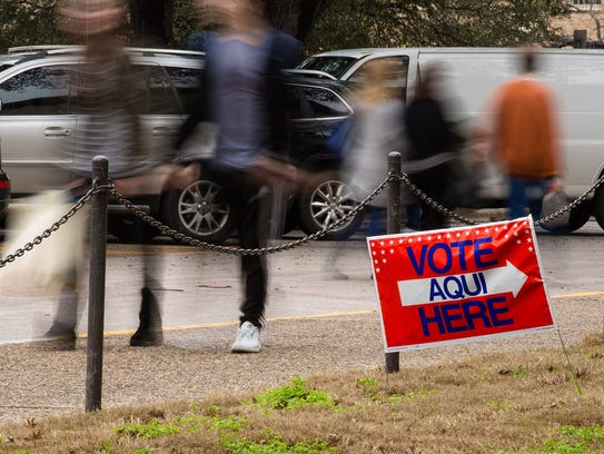 People walk past a polling place.