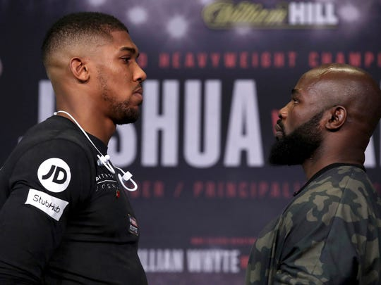 Britain's Heavyweight Champion Anthony Joshua, left, and  challenger Carlos Takam face-off during the press conference at the National Museum  in Cardiff Wales on Thursday Oct. 26, 2017. Joshua will take on Takam in a world title fight in Cardiff on Saturday.  (Nick Potts/PA via AP)