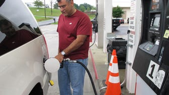 Samir Cook fills up his vehicle at a city-run station on Saturday, July 19, 2014, in Somerset, Ky. The station on the outskirts of Somerset opened to the public on Saturday, selling regular unleaded gas for $3.36 a gallon. In the first three hours, about 75 customers fueled up at the no-frills city station, where there are no snacks, no repairs and only regular unleaded gas. The cityís mayor says he hopes the no-frills station will lower gas prices around town. (AP Photo/Bruce Schreiner) ORG XMIT: RPBS101