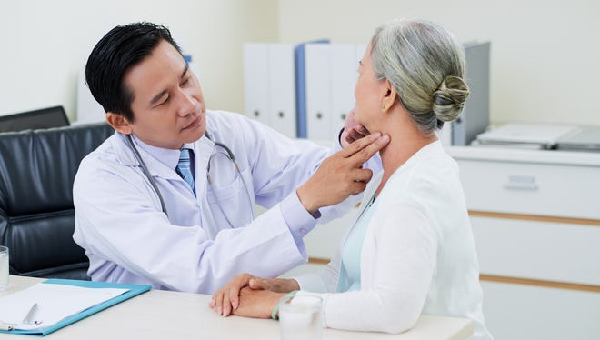 Doctor checking thyroid glands of senior woman.