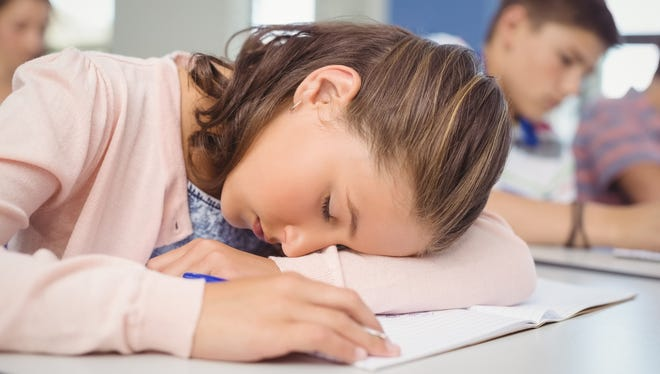 Tired student sleeping in classroom.