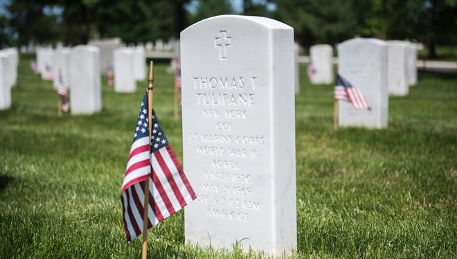An American flag sits in front of a headstone in Arlington National Cemetery.