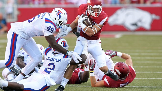 Arkansas Razorbacks wide receiver Drew Morgan (80) runs after a catch as Louisiana Tech Bulldogs defensive end Jaylon Ferguson 945) and safety Secdrick Cooper (2) attempt  to tackle at Donald W. Reynolds Razorback Stadium. Arkansas defeated Louisiana Tech 21-20. Mandatory Credit: Nelson Chenault-USA TODAY Sports