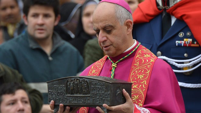 Italian archbishop Rino Fisichella holds the remains said to belong to St. Peter before a ceremony at the Vatican.