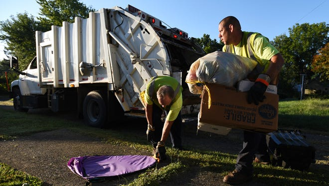 Brandon Johnson, right, and Larry Wood load a garbage truck early one morning. Johnson and Wood are part of four crews that head out every weekday morning, rain or shine, to collect the trash.