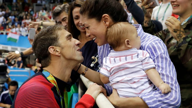 Aug. 9, 2016, file photo, U.S. swimmer Michael Phelps celebrates winning his gold medal in the men's 200-meter butterfly with  Nicole Johnson and baby Boomer Aug. 9, 2016, during the swimming competitions at the 2016 Summer Olympics, in Rio de Janeiro, Brazil. Phelps shared an Instagram picture on Oct. 30, 2016, of his beach wedding to Johnson that took place months after the couple got legally married in Arizona.