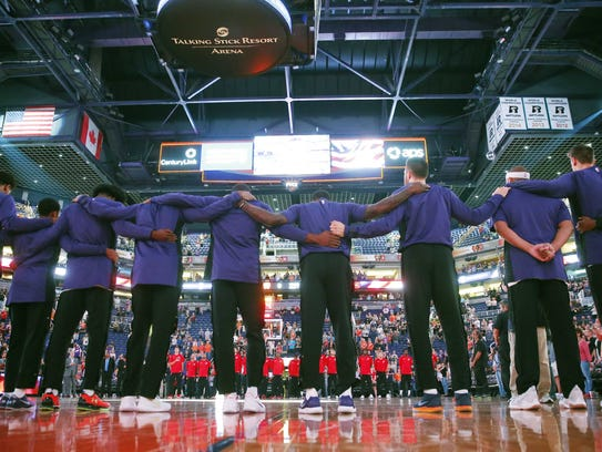 Phoenix Suns players put their arms around each other
