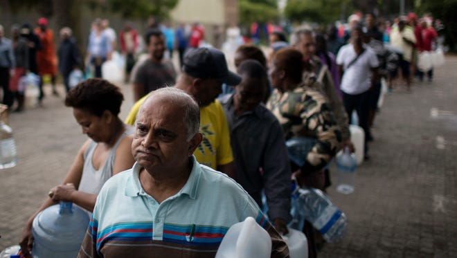 Residents queue to fill containers with water from a source of natural spring water in Cape Town, South Africa, Feb. 2, 2018.