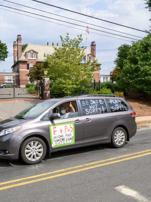 """A minivan participating in the """"School Safety First"""" car caravan passes the governor's mansion in Hartford on Thursday, July 30. About two dozen groups of teachers, parents and advocates held coordinated demonstrations on Thursday, demanding more funding to ensure schools can reopen safely during the continuing pandemic."""
