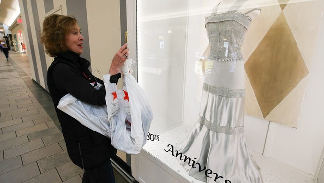 Dorothy Lopp takes a photo of one of the gowns worn by Patricia Barnstable-Brown that are on display at Oxmoor Mall.  March 26, 2018