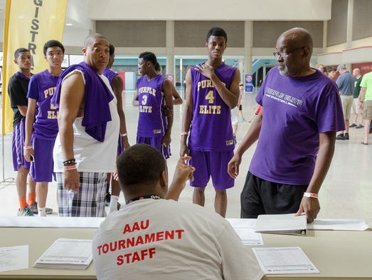 Anthony Cooper, center, helps Coach Mwalimu Keita of the Purple Elite team, right, as they register for the Amateur Athletic Union (AAU) Boys Basketball Elite Tournaments in the North Wing of the Kentucky Exposition Center. July 22, 2014