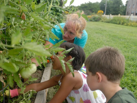 New Roots Youth Garden volunteer Carol Selby helps