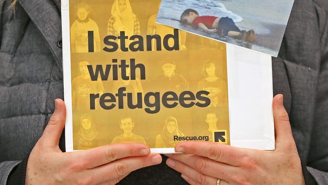 A woman holds a sign showing support of refugees and a famous photo of a drowned Syrian boy whose body had washed ashore, in 2015, during the protest at the Indianapolis Airport, Sunday, January 29, 2017, against President Donald Trump's executive orders on immigration.  The photo symbolizes the grave nature of the refugee crisis.