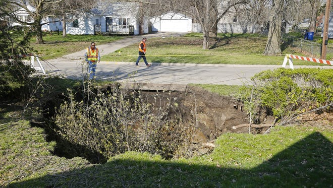 City workers inspect the area where a sinkhole formed Aprilo 13 in front of a house on Southwest Fifth Street.