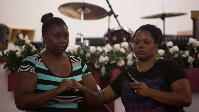 Kimberly Thomas, right, holds the mic for Nicole McMiller, as she gets emotional while speaking at the vigil for Stef'An Strawder at St. Mary's Missionary's Baptist Church on July 25, 2016, in Fort Myers, Florida. Stef'An was killed in a shooting at Club Blu the night before.