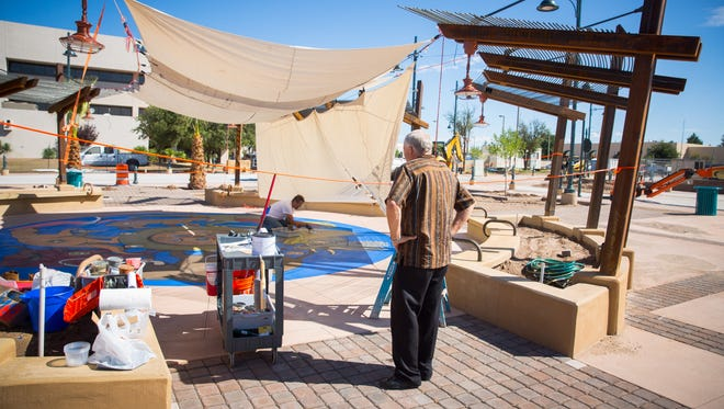 Las Cruces plaza architect Steve Newby, right, watches artist Bob Diven paint dinosaurs on the base of the plaza's splash pad, Saturday, Aug. 27, 2016. The official plaza opening is scheduled for Sept. 17, 2016, though the city will hold its Sept. 11Patriot Day festivities on the plaza.