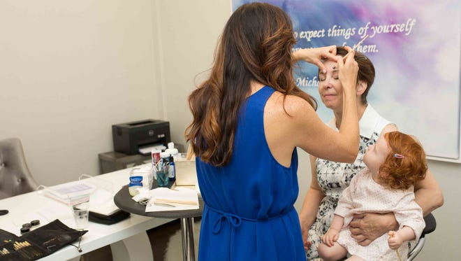 Tammy Fisher, master brow artist, does Lillian Campbell's brows for EvolveMKD's family day event on July 22. Campbell, mother of Evolve employee Joanna Campbell, holds granddaughter Eleanor Hoffman on her lap.