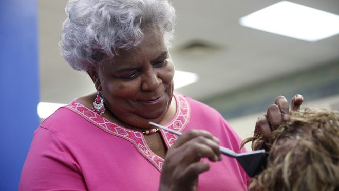 Annie Ford works with a client at Suburban Salon Tuesday, Feb. 27, 2018. Ford was the first black hairdresser at Suburban at a time when few salons had integrated staffs.