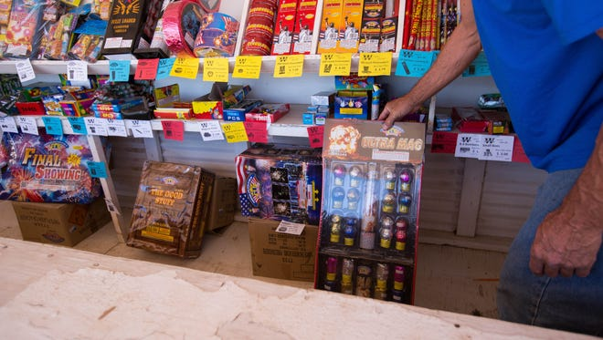 Robert Lewis, a sales person at the Mr. W's fireworks stand on the Otero County side of Chaparral , showing the types of ariel fireworks that are for sale in Otero County but not in Doña Ana County, Wednesday July 4, 2018.