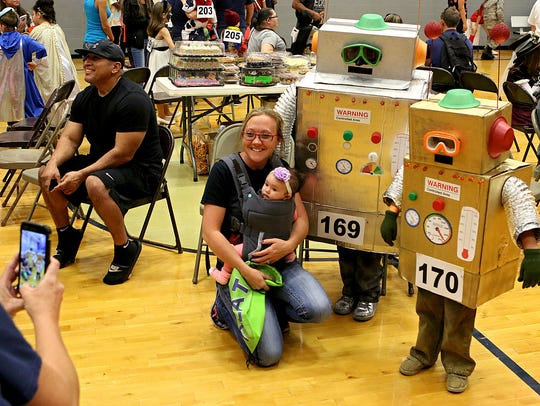A pair of robots pose for photos at the city of Wichita