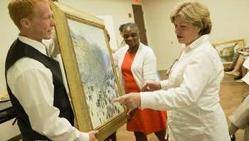 Marilyn McNeil, vice president and director of athletics at Monmouth University, looks at art work with volunteers Hayden Audy and Sarah Davis, a student in the MSW program at Monmouth University