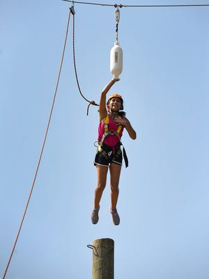 Jasmine Lopez leaps off a pole 27 feet high to hit a target during the St. Cloud Youth Leadership Academy Thursday, Aug. 24, at Camp Courage near Annandale.