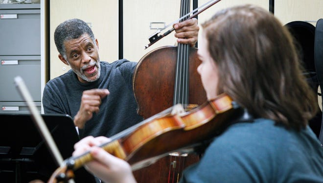 Norman Johns, CSO cellist, critiques the violin technique of Meghan Long, 15, a sophomore at the School for Creative and Performing Arts.