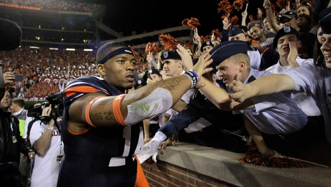 Auburn quarterback Nick Marshall (14) celebrates with fans after the No. 9 Tigers beat Georgia 43-38 on a remarkable play with less than a minute left Saturday at Jordan Hare Stadium.