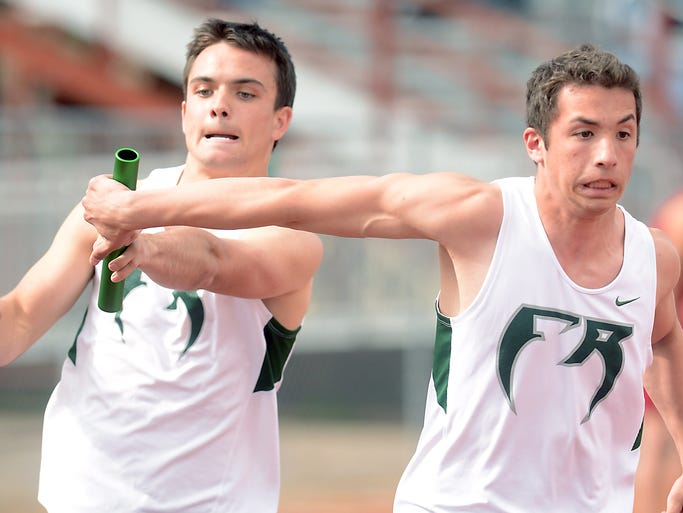 Fossil Ridge sprinter, Joey Campain, left, hads the baton to Zack Feuer, during the 4 x 200 relay, during the Golden Spike track meet at French Field Wednesday April 9, 2014.