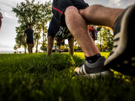 Participants of a Pride Center of Vermont running group stretch at Burlington's Waterfront Park Tuesday night before heading on their three-mile run.