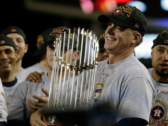 In this Nov. 1, 2017, photo, Houston Astros manager A.J. Hinch holds the championship trophy after Game 7 of baseball's World Series against the Los Angeles Dodgers.