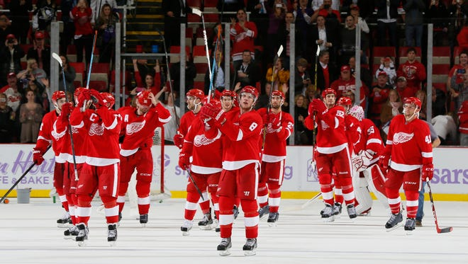 Detroit Red Wings raise the sticks to salute the crowd after Justin Abdelkader, center, scored the overtime game winning goal for a 4-3 win over the Pittsburgh Penguins in Detroit on Thursday, October 23, 2014