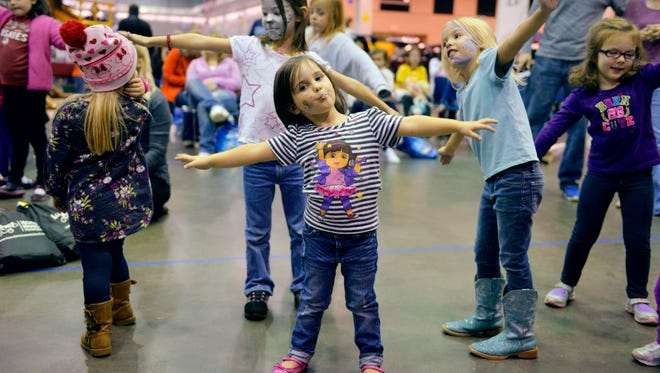 Children put out their arms and pretend to fly as they listen to the Teddy Bear Band at Saturday's Kids & Parents Expo.
