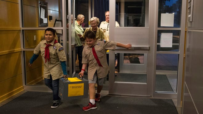 Elijah Skilbred, 11, (left) and Jacob Schillerstrom, 11, carry the ballot box into the Instructional Planning Center on Tuesday, Sept. 18, 2018 in Sioux Falls, S.D.